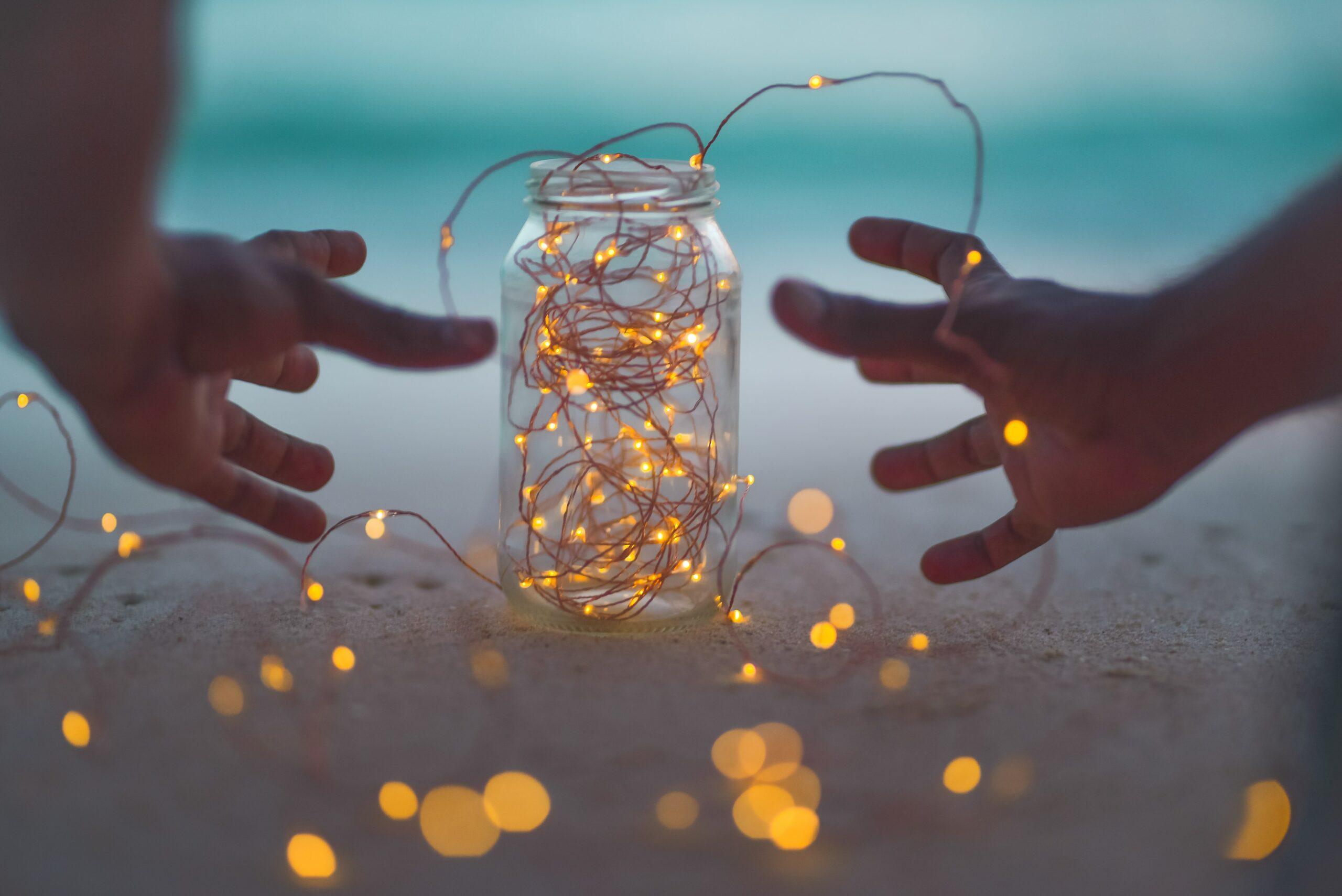 2 mains autour d'un bocal avec lumières autour