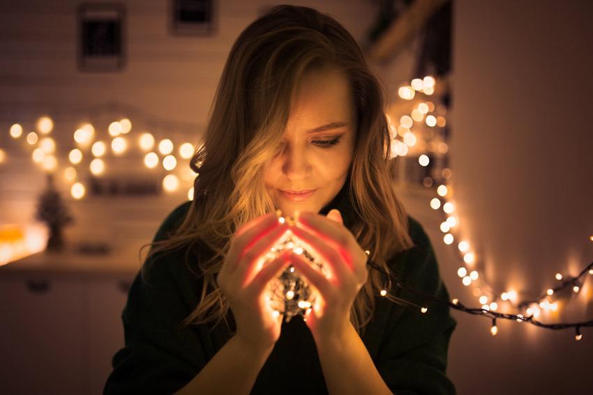 Femme heureuse qui tient une lumière entre ses mains